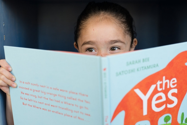 Young girl looks over the top edge of a picture book