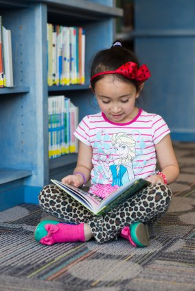 Child sitting on floor of library, reading book
