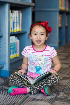 Kid smiles while reading to herself