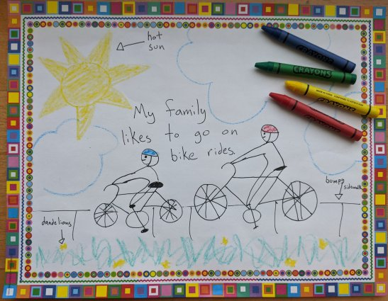 Image depicts a drawing of two people biking on a sidewalk next to grass and dandelions. There are crayons lying on the paper.
