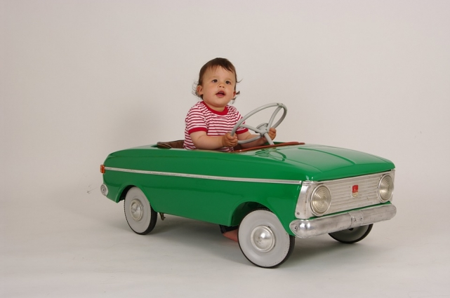Child driving in a toy car