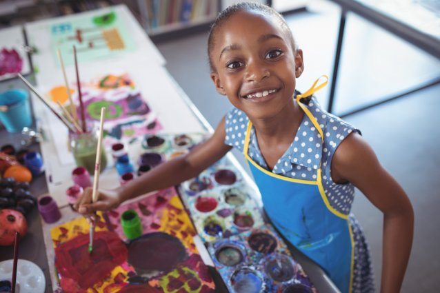 Child smiles at the camera while painting