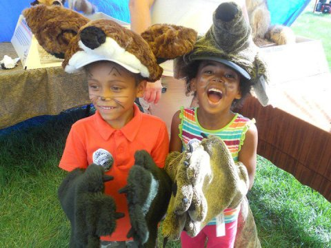 Two children laughing and playing dress up in animal costumes.