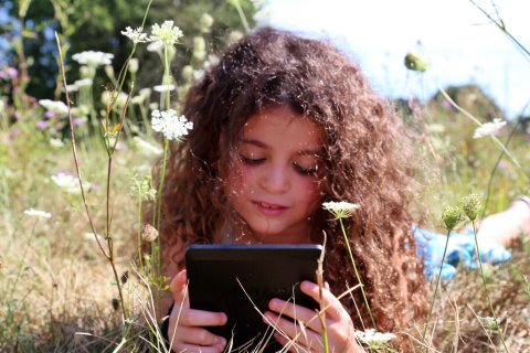 Child uses tablet outside
