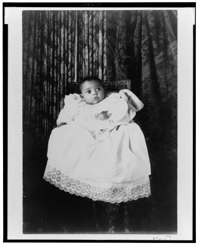 Full length portrait of African American baby wearing christening gown