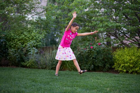 Young girl in grass about to do a cartwheel