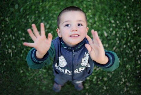 Shot from above of a little boy standing in grass reaching his hands up to the sky