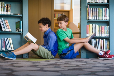 Two boys sitting back-to-back while reading