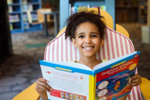 Child smiling at camera, sitting in chair and reading book