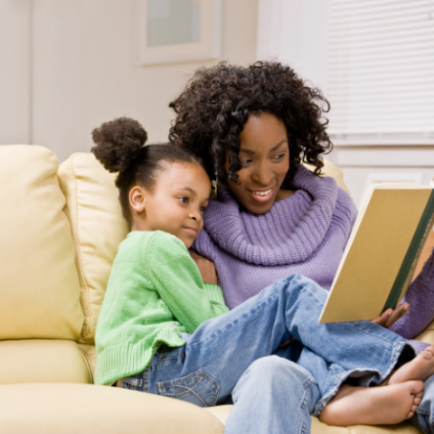A grownup and child, snuggle on a couch, reading together.