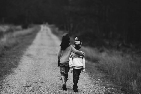 Two children seen from the back, walking with their arms around each other