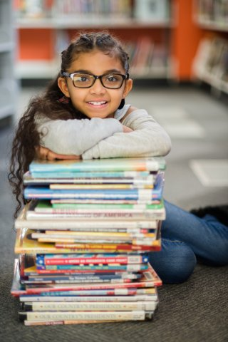 Girl leaning on a pile of books