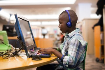 Child with headphones using computer