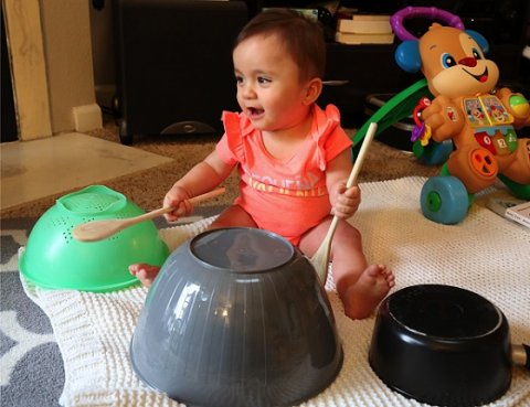 Toddler playing drums with pots and wooden spoons