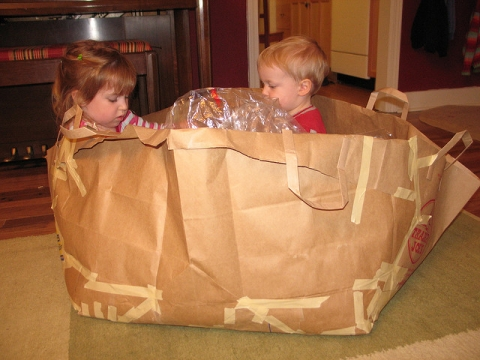 Children playing in boat made from paper sacks and tape