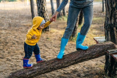 Toddler and adult hold hands while walking up a fallen tree trunk, only adult legs visible