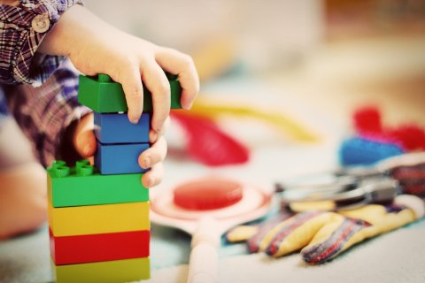 Toddler stacking large Lego blocks