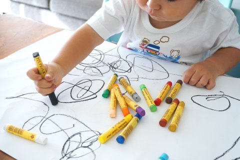 Toddler scribbling with crayons