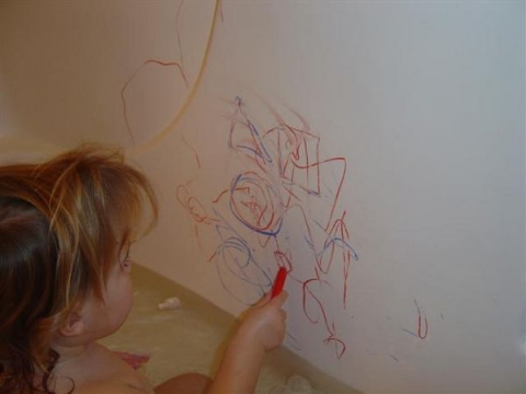 Chid drawing in bathtub