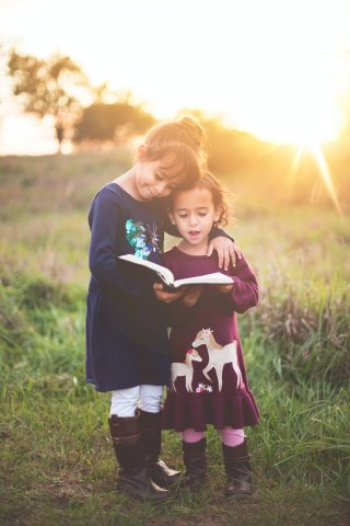 Two young children standing outside reading a book together