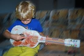 Boy playing a homemade guitar