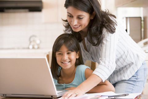 Parent and child use laptop computer together