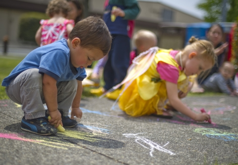 A preschool boy and girl draw with chalk on asphalt.