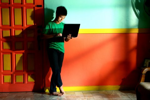 Young person standing while using a laptop computer