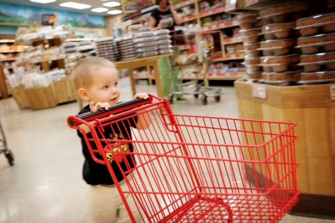 Child pushing small grocery cart