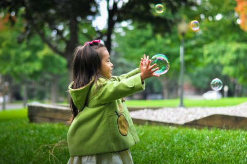 a small child playing with bubbles outside