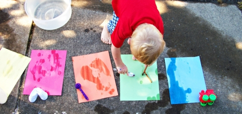 Child painting paper with water