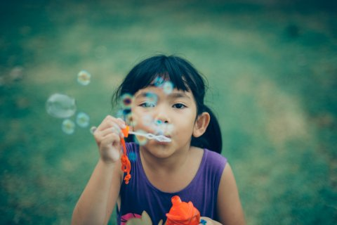 Child blows a bubble