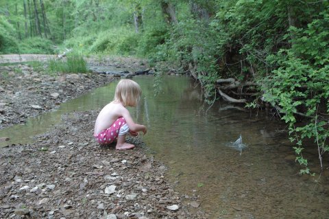 Child throwing rocks in the water