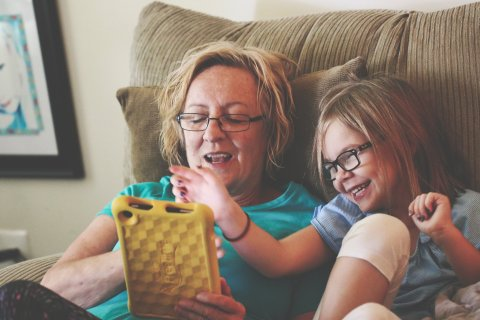 Caregiver and child use tablet together